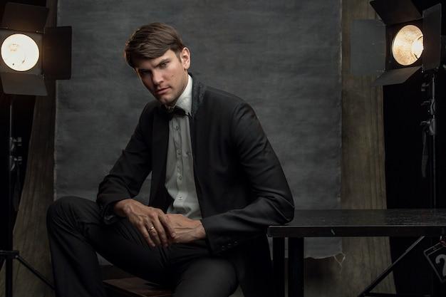 Ritratto degli uomini bei in vestito nero in studio che si siede sul fondo della tela. stile ritratto di hollywood