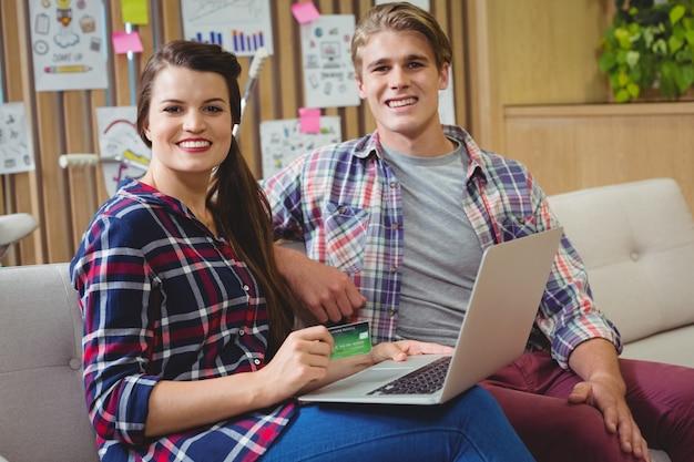 Ritratto degli uomini d'affari che fanno spesa online sul computer portatile