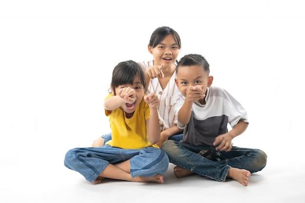 Ritratto dei bambini svegli tailandesi asiatici divertenti che si siedono indicare isolato su fondo bianco