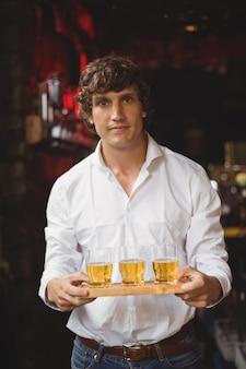 Ritratto dei baristi che tengono i vetri di colpo del whiskey al contatore della barra
