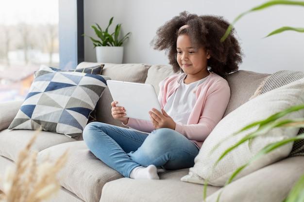 Ritratto dei cartoni animati di sorveglianza della ragazza sul sofà