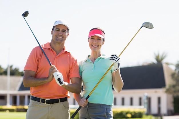 Ritratto dei club di golf sorridenti della tenuta delle coppie