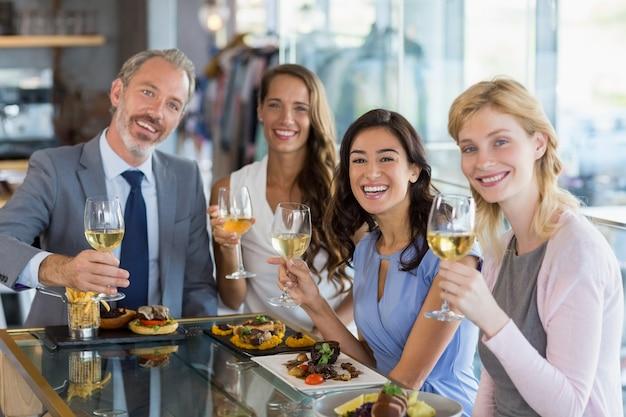 Ritratto dei colleghi felici di affari che tengono i vetri di birra mentre pranzando