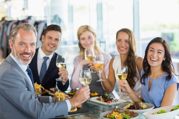 Ritratto dei colleghi felici di affari che tostano i vetri di birra mentre pranzando