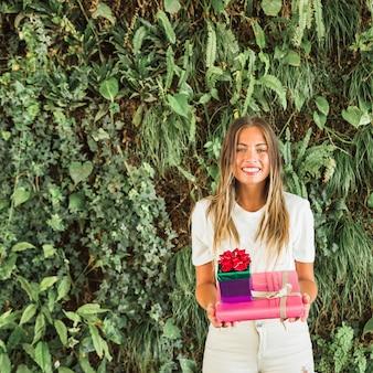 Ritratto dei contenitori di regalo sorridenti di una tenuta della donna davanti alle foglie verdi