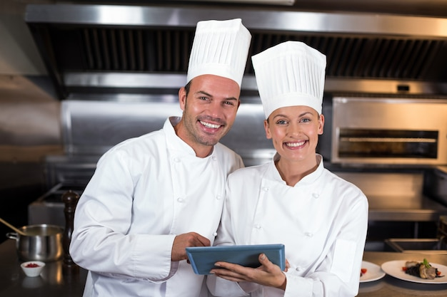 Ritratto dei cuochi unici felici che tengono lavagna per appunti in cucina