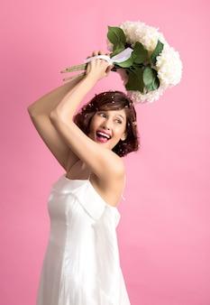 Ritratto dei fiori svegli allegri sorridenti di una tenuta della donna isolati sul rosa