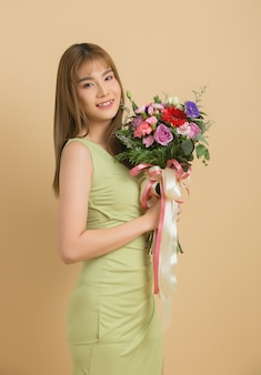 Ritratto dei fiori svegli allegri sorridenti di una tenuta della donna