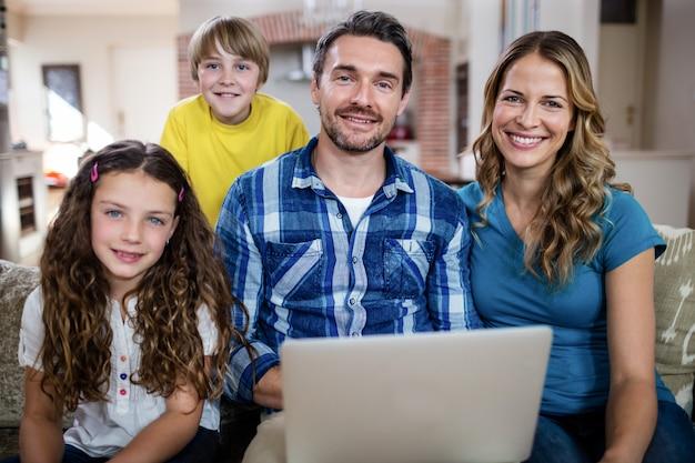 Ritratto dei genitori e dei bambini che per mezzo del computer portatile