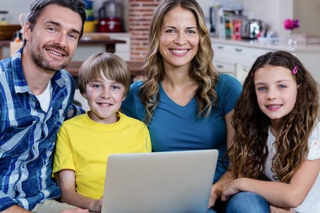 Ritratto dei genitori e dei bambini che si siedono sul sofà e che per mezzo di un computer portatile
