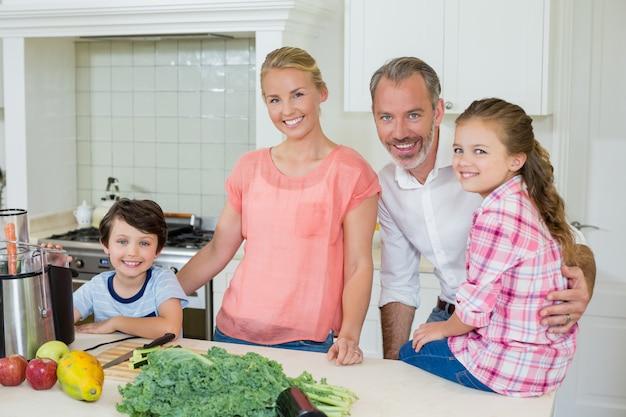 Ritratto dei genitori e dei loro due bambini che stanno nella cucina