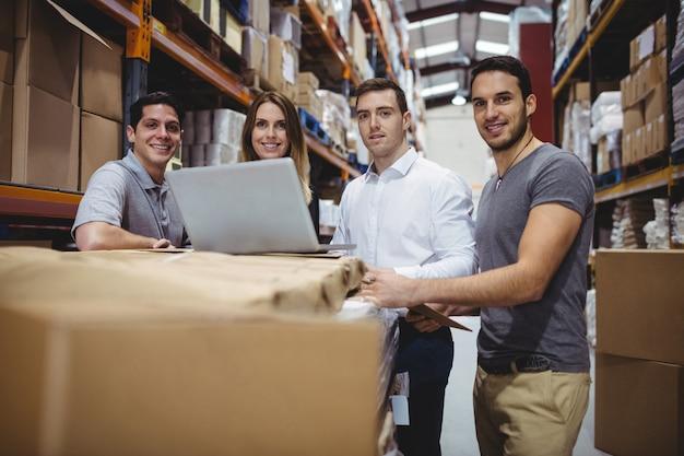Ritratto dei gestori di magazzino sorridenti che per mezzo del computer portatile