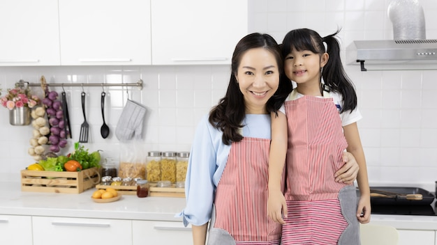 Ritratto dei grembiuli d'uso della famiglia asiatica nella cucina