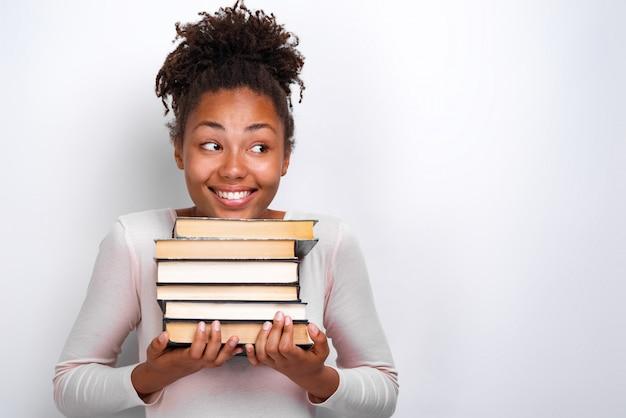 Ritratto dei libri felici della tenuta della ragazza del nerd sopra bianco. di nuovo a scuola