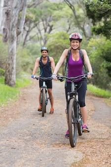 Ritratto dei motociclisti che guidano bici in foresta