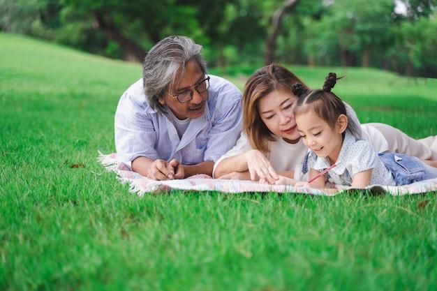 Ritratto dei nonni e della nipote asiatici che mettono sul campo di vetro verde all'aperto, famiglia che gode insieme del picnic nel concetto di giorno di estate