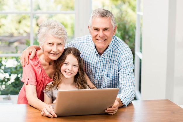 Ritratto dei nonni e della nipote sorridenti che per mezzo del computer portatile a casa