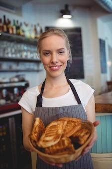 Ritratto dei pani d'offerta della cameriera di bar felice in caffetteria