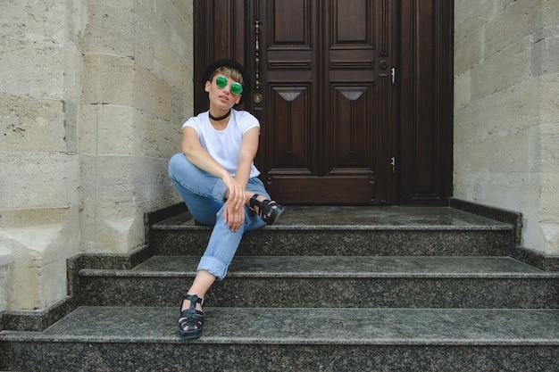 Ritratto dei pantaloni a vita bassa femminili con trucco naturale e breve taglio di capelli che godono del tempo libero all'aperto