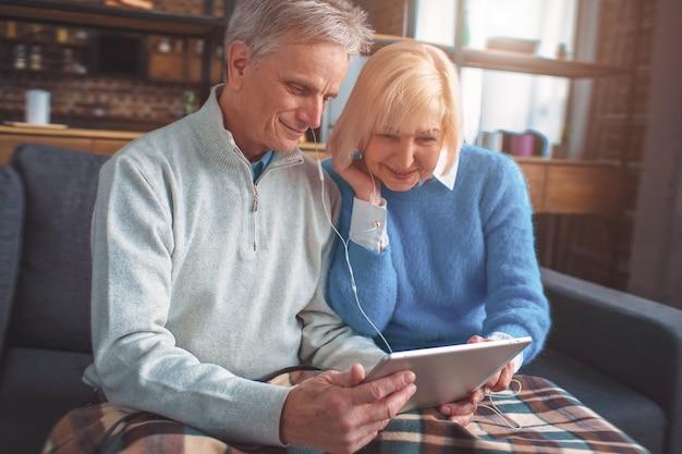 Ritratto dei pensionati che guardano film sul tablet e che utilizzano le cuffie