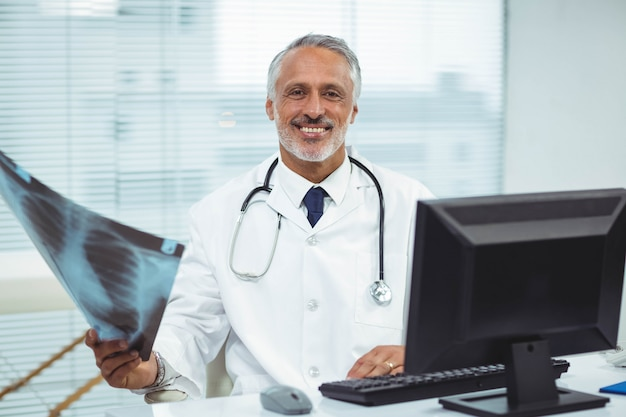 Ritratto dei raggi x felici della tenuta di medico in clinica