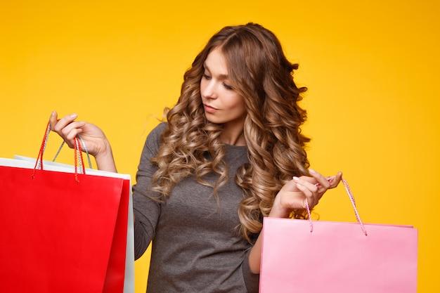 Ritratto dei sacchetti della spesa felici sorpresi di una tenuta della ragazza