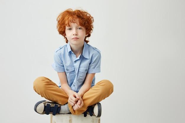 Ritratto del bambino annoiato con capelli rossi e le lentiggini che si siedono sulla scatola con espressione infelice
