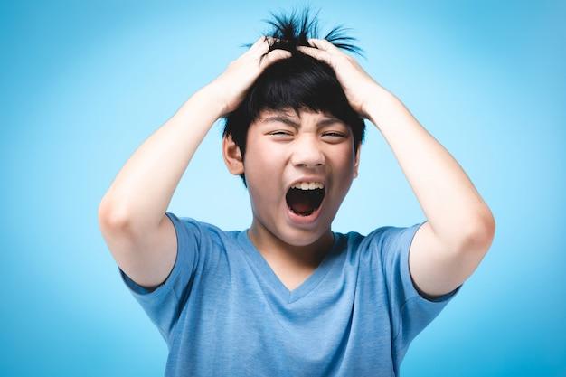 Ritratto del bambino asiatico arrabbiato sul blu.