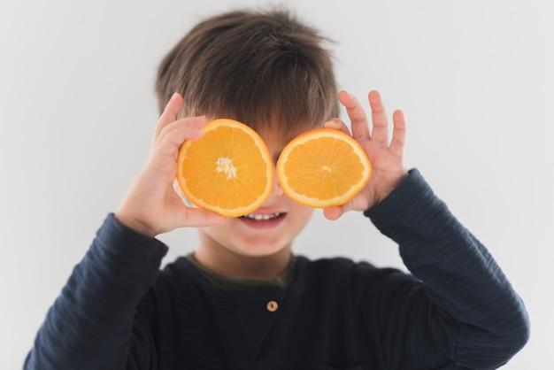 Ritratto del bambino che tiene le metà arancio sopra gli occhi