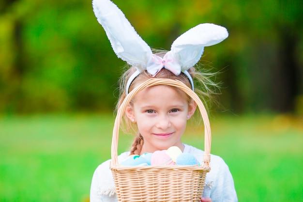 Ritratto del bambino con il busket di pasqua con le uova all'aperto