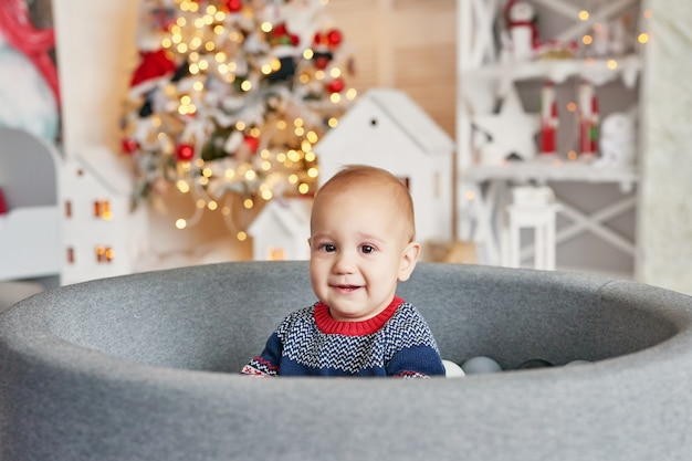 Ritratto del bambino del bambino con l'albero di natale. natale carino bambino. concetto di vacanza in famiglia. sala giochi per bambini. natale nella stanza dei bambini.
