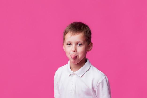 Ritratto del bambino del ragazzo che attacca fuori la sua lingua sul contesto rosa