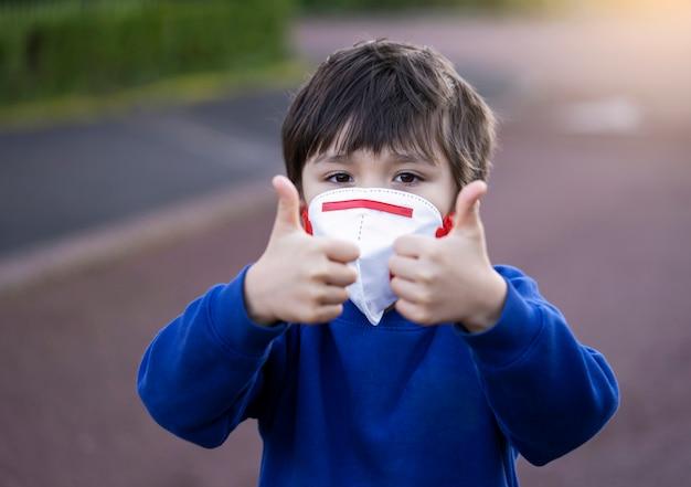 Ritratto del bambino della scuola che indossa la maschera protettiva per l'inquinamento o il virus, bambino in uniforme scolastica che indossa la maschera di protezione e che mostra i pollici su mentre aspettando lo scuolabus di mattina.