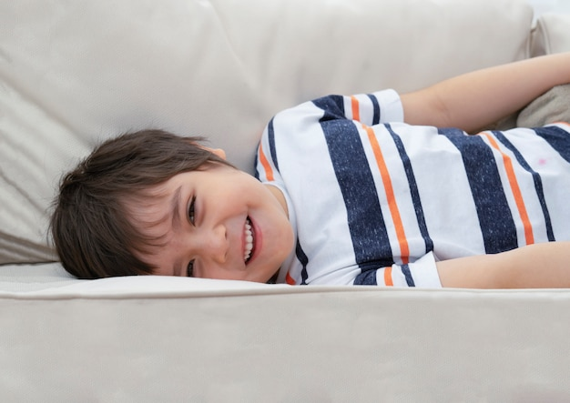 Ritratto del bambino positivo che si trova giù sul sofà che esamina macchina fotografica con il fronte sorridente