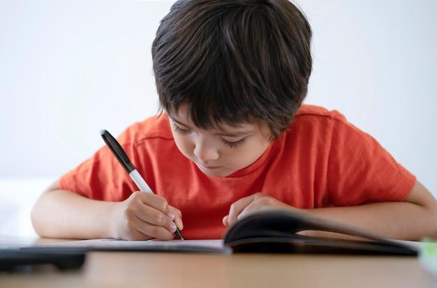 Ritratto del bambino prescolare che fa i compiti. concetto di educazione