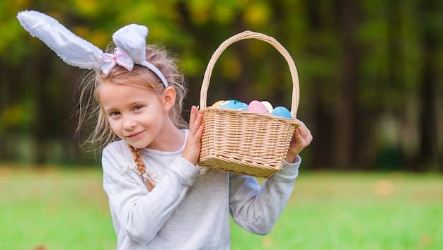 Ritratto del bambino su pasqua con le uova all'aperto