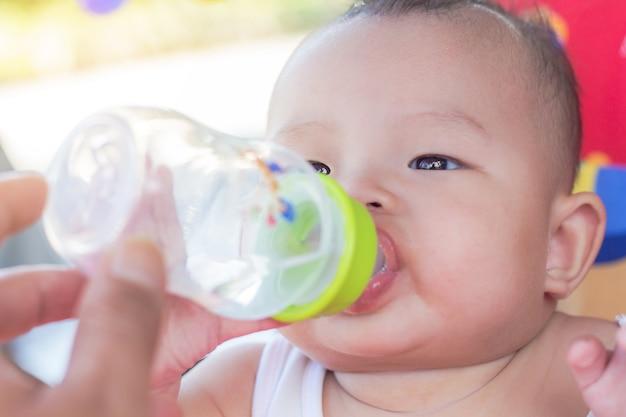 Ritratto del bambino sveglio sull'acqua potabile dell'automobile del giocattolo della bottiglia
