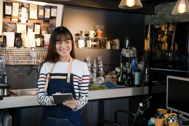 Ritratto del barista asiatico sorridente che tiene compressa digitale al contatore in caffetteria
