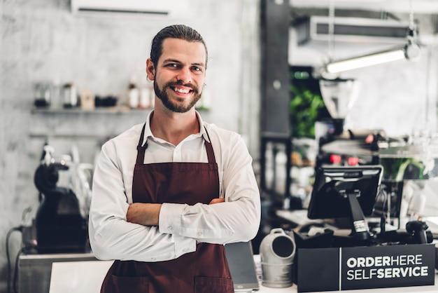 Ritratto del barista barbuto bello uomo piccolo imprenditore sorridente dietro il bancone in un caffè