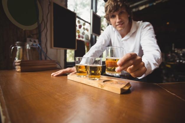 Ritratto del barista che tiene bicchiere di whisky al bancone del bar