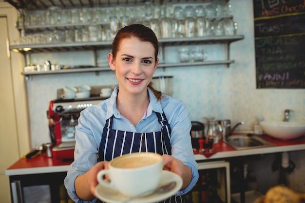 Ritratto del barista felice che offre caffè al caffè