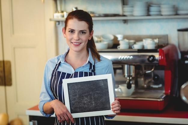Ritratto del barista felice che tiene lavagna in bianco al caffè