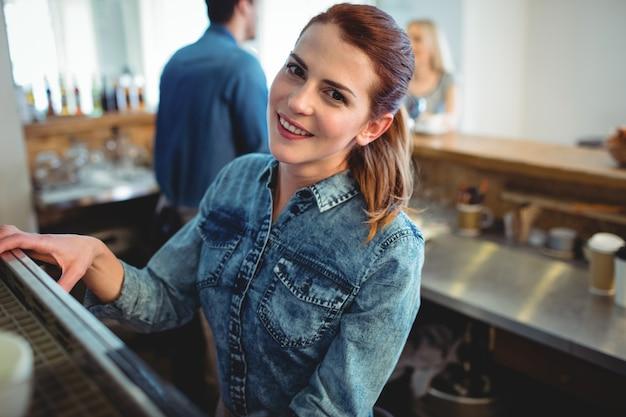 Ritratto del barista felice con il collega e il cliente al caffè