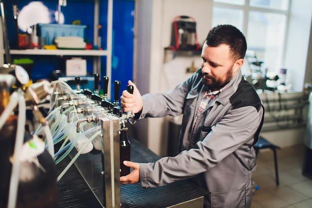 Ritratto del birraio che produce birra sul suo posto di lavoro nel birrificio