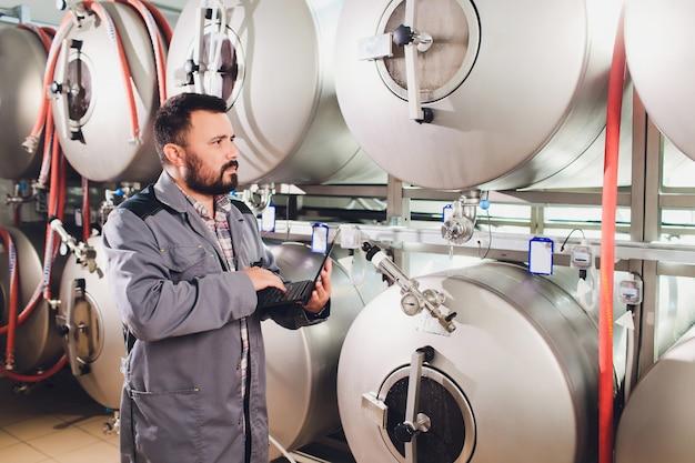 Ritratto del birraio che sta preparando la birra sul posto di lavoro nella birreria.