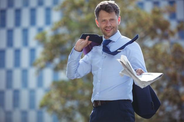 Ritratto del blazer e del giornale della tenuta dell'uomo d'affari