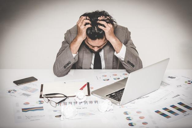 Ritratto del burnout sottolineato dell'uomo d'affari che tiene la sua testa con entrambe le mani sul lavoro