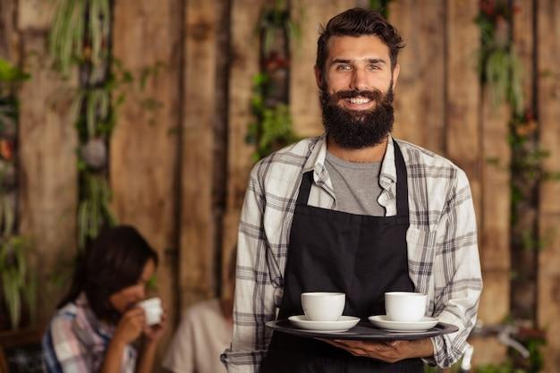 Ritratto del cameriere che tiene una tazza di caffè in vassoio del servizio