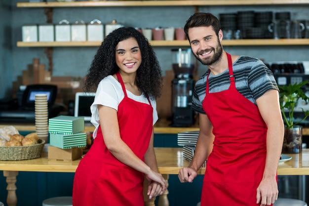 Ritratto del cameriere e della cameriera di bar sorridenti che si appoggiano al contatore