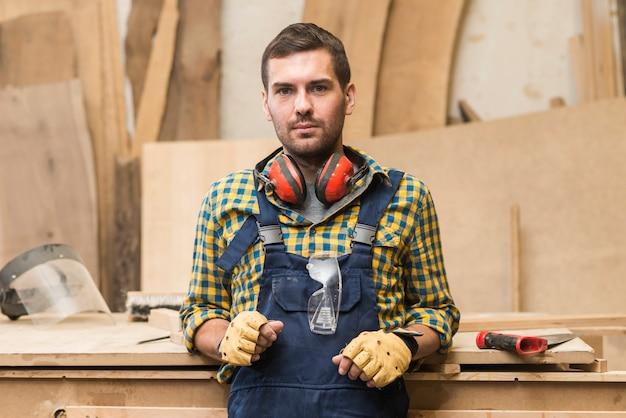 Ritratto del carpentiere maschio serio con il difensore di orecchio intorno al suo collo